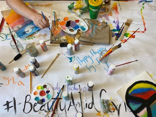 Self-care painting activity set up for staff members, arm with a paint brush dips into paint